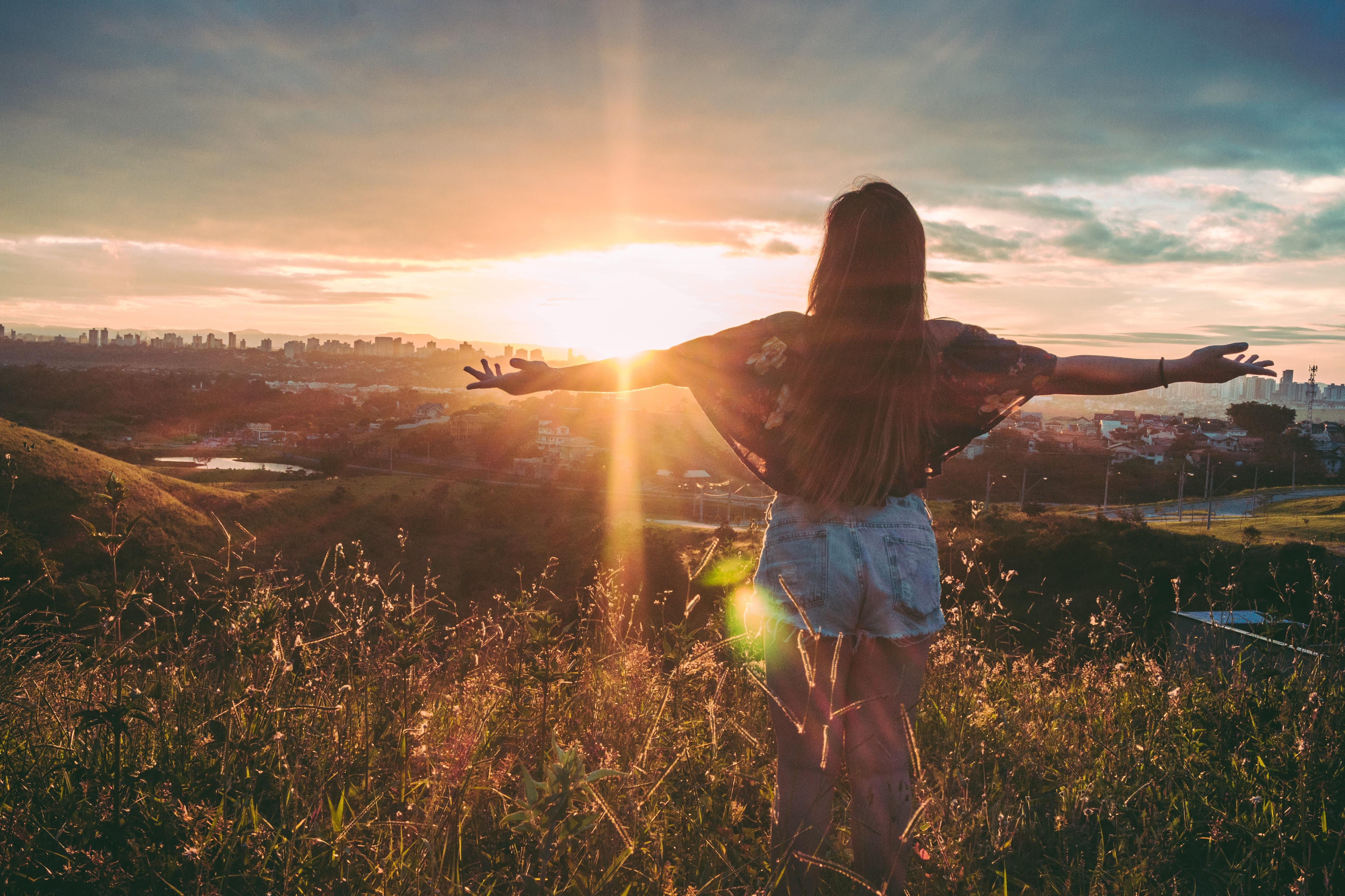 vrouw armen gespreid met zon