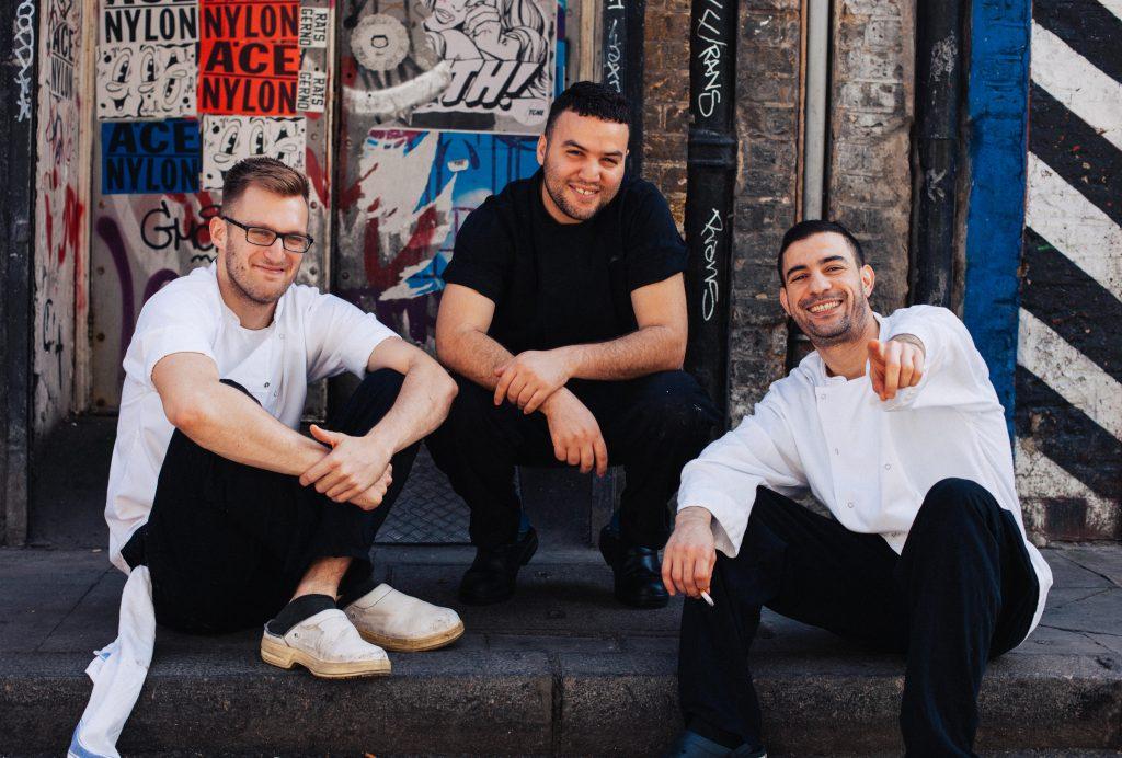 drie jongens zitten op de stoep